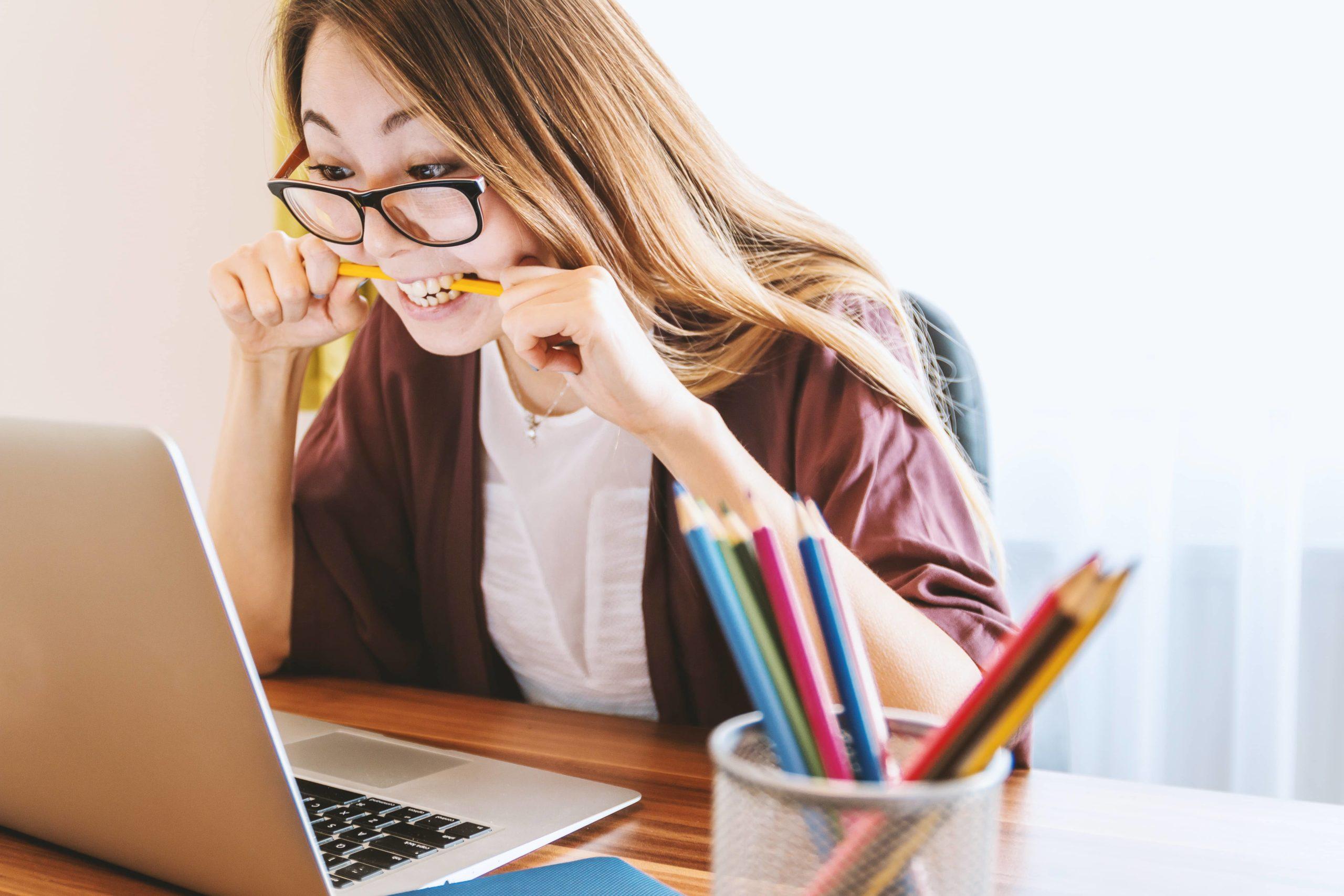 Femme-nerveuse-crayon-entre-les-dents-regarde-son-ordinateur-portable