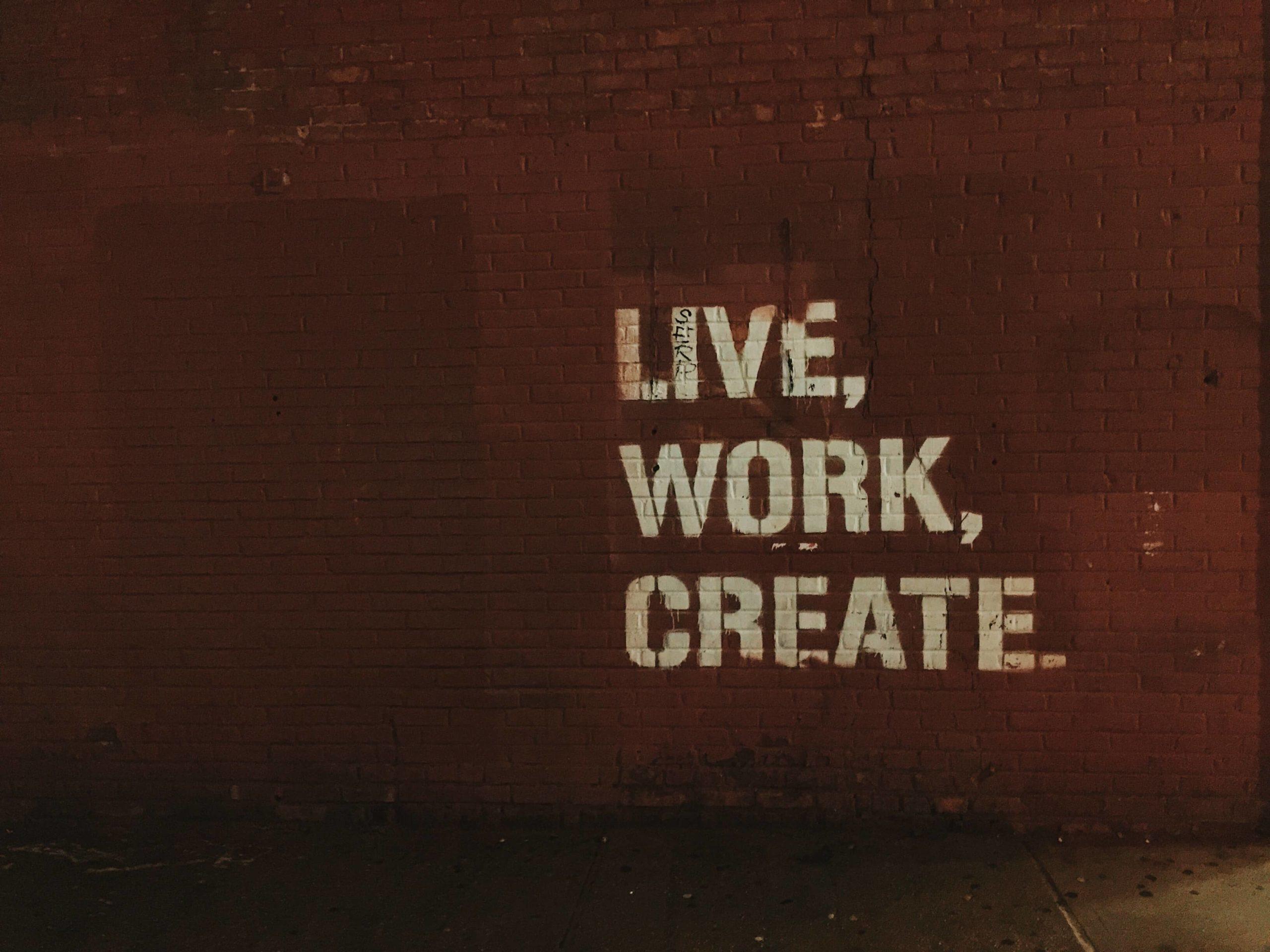 Tag-en-blanc-sur-mur-en-brique-orange-écrit-Live-Work-Create