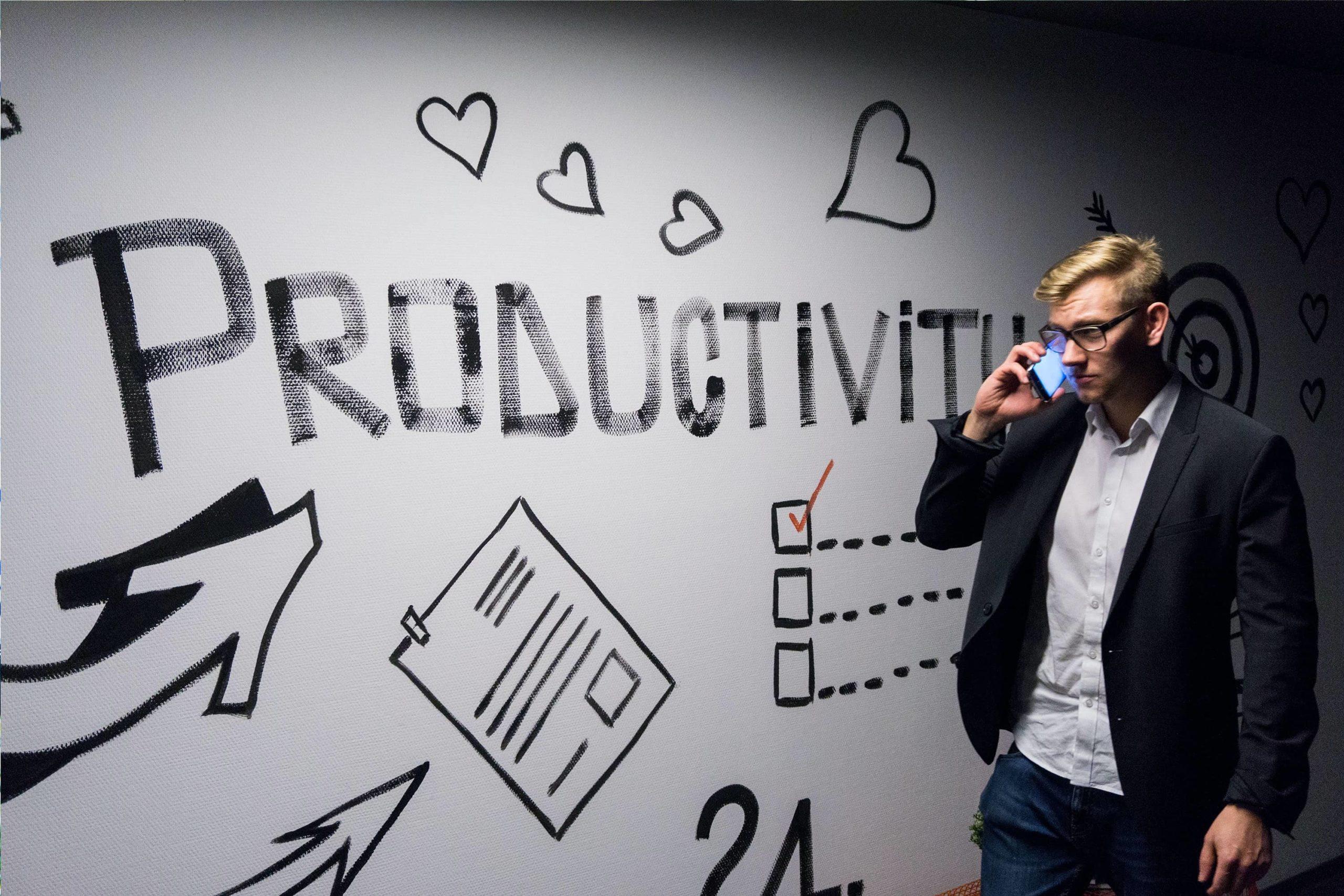 Homme au téléphone devant mur de dessins de productivité